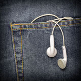 Headphones hanging off a jeans pocket. Royalty Free Stock Images