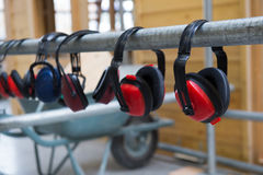 Headphones for hearing safety. Headphones hanging in a row for hearing safety stock photo