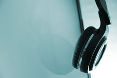 Headphones hanging on a screen. Stock Image