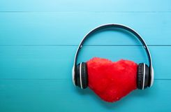 Headphones and heart shape listening music on blue wooden background, earphone with audio radio