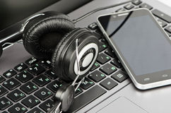 Headphones, keyboard and smartphone Royalty Free Stock Photos