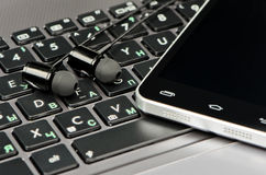 Headphones, keyboard and smartphone Royalty Free Stock Images