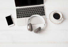 Headphones, laptop computer, mobile phone and cup of coffee. Wireless headphones, laptop computer, mobile phone and cup of coffee stock image