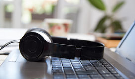 Headphones on laptop keyboard Royalty Free Stock Image