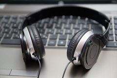 Headphones on laptop keyboard Stock Image