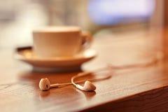 Headphones lying near cup of coffee Stock Photography