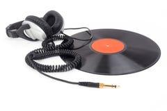 Headphones lying over vinyl record Royalty Free Stock Image