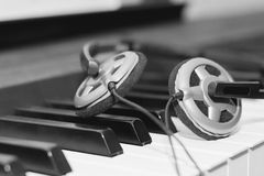 Headphones lying on the piano keys Stock Images