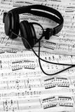 Headphones lying on sheet music Stock Photos