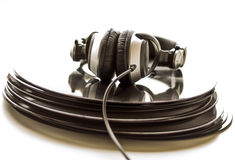 Headphones lying on the stack of vinyl records. Stock Photo