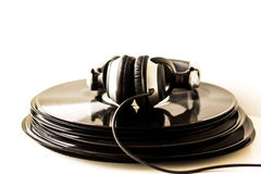 Headphones lying on the stack of vinyl records. Stock Photos