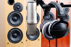 Headphones and microphone. In sound studio on a background of acoustic systems Stock Photo