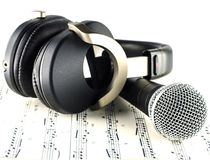 Headphones and Microphone. On Musical notes - music concept Stock Images