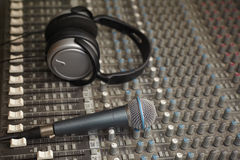 Headphones and microphone on old dirty sound mixer Stock Photography