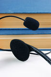 Headphones with a microphone and a stack of books Royalty Free Stock Image