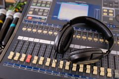 Headphones, microphones, amplifying equipment, Studio audio mixer knobs and faders, background sound mixer. Workplace and stock images
