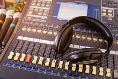 Headphones, microphones, amplifying equipment, Studio audio mixer knobs and faders, background sound mixer. Workplace and stock image