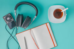 Headphones with misic player. And cup of tea on plain aquamarine background Stock Photo