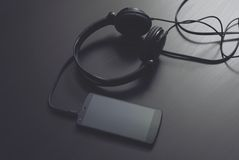 Headphones. With mobile smartphone on the table Stock Photos