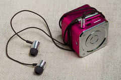Headphones and mp3 player at the flax background. Stock Images