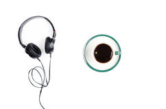 Headphones with mug of coffee on a white background. Stock Image