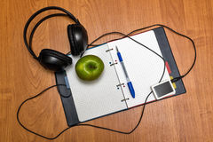 Headphones, music player, pen and apple lie on notebook. School. Royalty Free Stock Photography