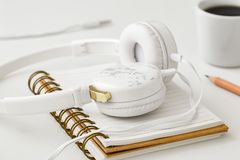 Headphones on notebook on white table royalty free stock images
