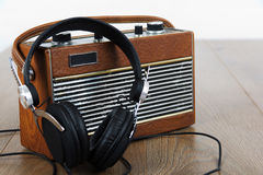 Headphones and old radio on wooden surface Royalty Free Stock Images