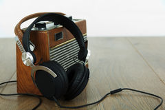 Headphones and old radio on wooden surface Royalty Free Stock Image