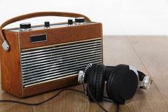 Headphones and old radio on wooden surface Royalty Free Stock Photo