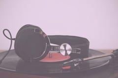 Headphones on an old retro record player Vintage Retro Filter. Stock Photos