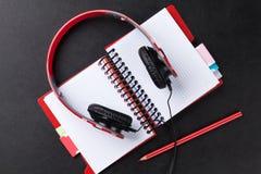 Headphones over notepad on desk Stock Photo