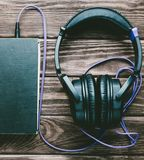Headphones with a paper book. Stock Photo