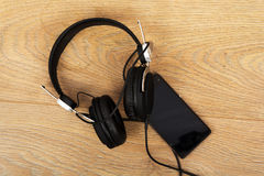 Headphones and phone on a wooden surface Stock Images
