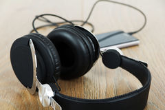 Headphones and phone on a wooden surface Stock Image