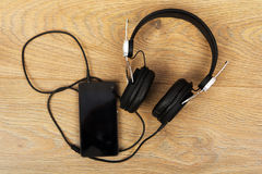 Headphones and phone on a wooden surface Royalty Free Stock Photos