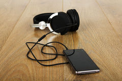 Headphones and phone on a wooden surface Royalty Free Stock Images