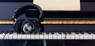 Headphones on piano keyboard, front view Stock Photography