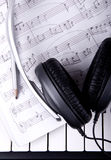 Headphones on piano and notebook Royalty Free Stock Photo