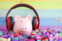 Headphones. On piggybank on colourful confetti Stock Photography
