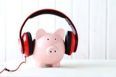 Headphones on piggybank Royalty Free Stock Photos