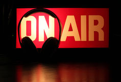 Headphones Podcast On-Air. Headphones silhouette against On-Air sign symbolizing a podcast broadcast