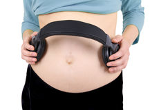 Headphones on a pregnant woman abdomen Royalty Free Stock Image