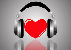 Headphones and red heart on the silver background closeup with reflection. Stock Photo