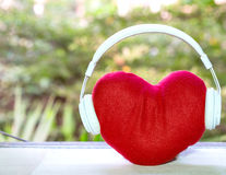 Headphones with red heart on table. music of love.