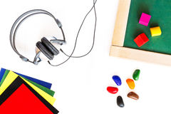 Headphones, school board, colored blocks, wax crayons, colored paper lying on a white wooden background. Headphones for studying l Royalty Free Stock Images
