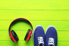 Headphones. With shoes on a green wooden table, close up Royalty Free Stock Photos