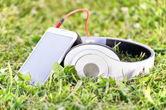 Headphones and smart phone on a meadow. Close-up shot of headphones and a smart phone on a meadow Royalty Free Stock Photo