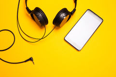 Headphones and smart pnone on yellowl bakground. Headphones and smart pnone on colorful bakground. Concept of living with music Royalty Free Stock Photos