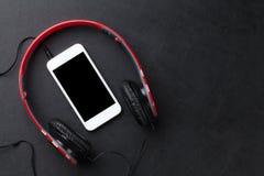 Headphones and smartphone on desk Stock Photos